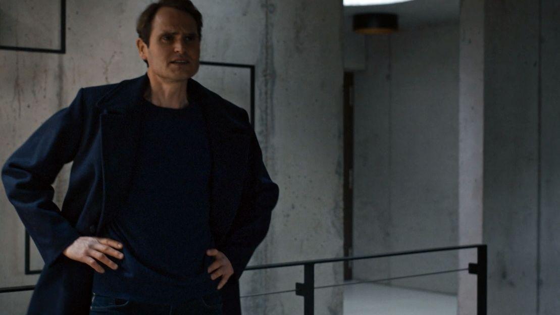 Ein dunkel gekleideter Mann mit Händen an den Hüften steht vor einer grauen Betonwand.