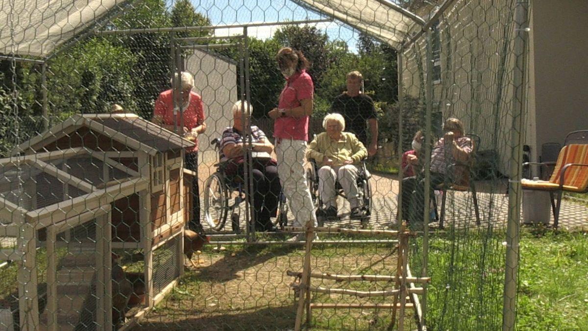 Bewohnerinnen eines Harburger Pflegeheims sitzen vor einem Hühnerauslauf.