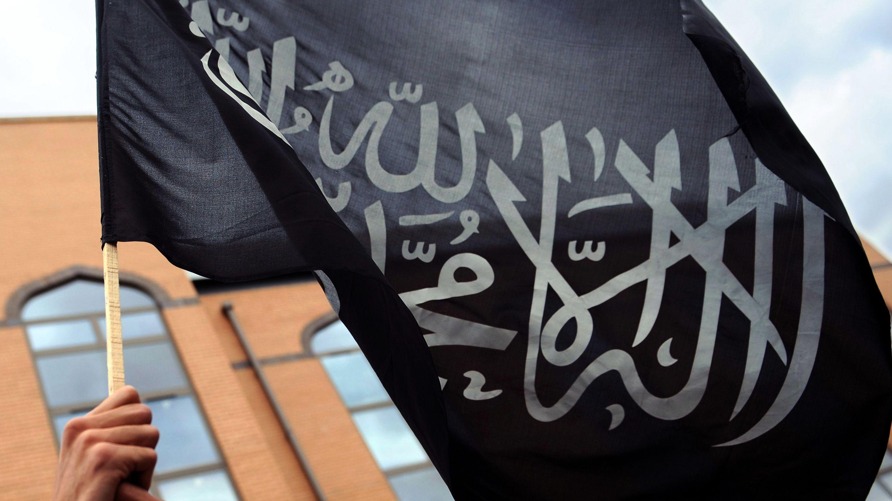 Ein britischer Muslim hält am 11.12.2009 bei einer Demonstration vor der Harrow Moschee eine islamische Fahne mit dem Glaubensbekenntnis, der sogenannten Schahada in die Höhe. Auf der Flagge ist das islamische Glaubensbekenntnis in arabischer Kalligraphie «Es gibt keinen Gott außer Allah und Mohammed ist sein Prophet» zu sehen. Die Terrormiliz Islamischer Staat (IS) verwendet die Schahada auf schwarzem Grund und dem zusätzlich abgebildeten mutmaßlichen Siegel Mohammeds.