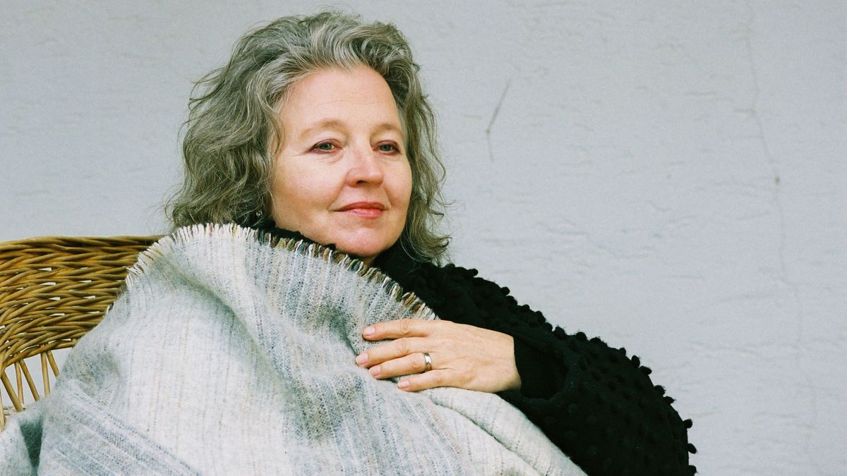 Schauspielerin sitzt mit Wolldecke im Korbsessel