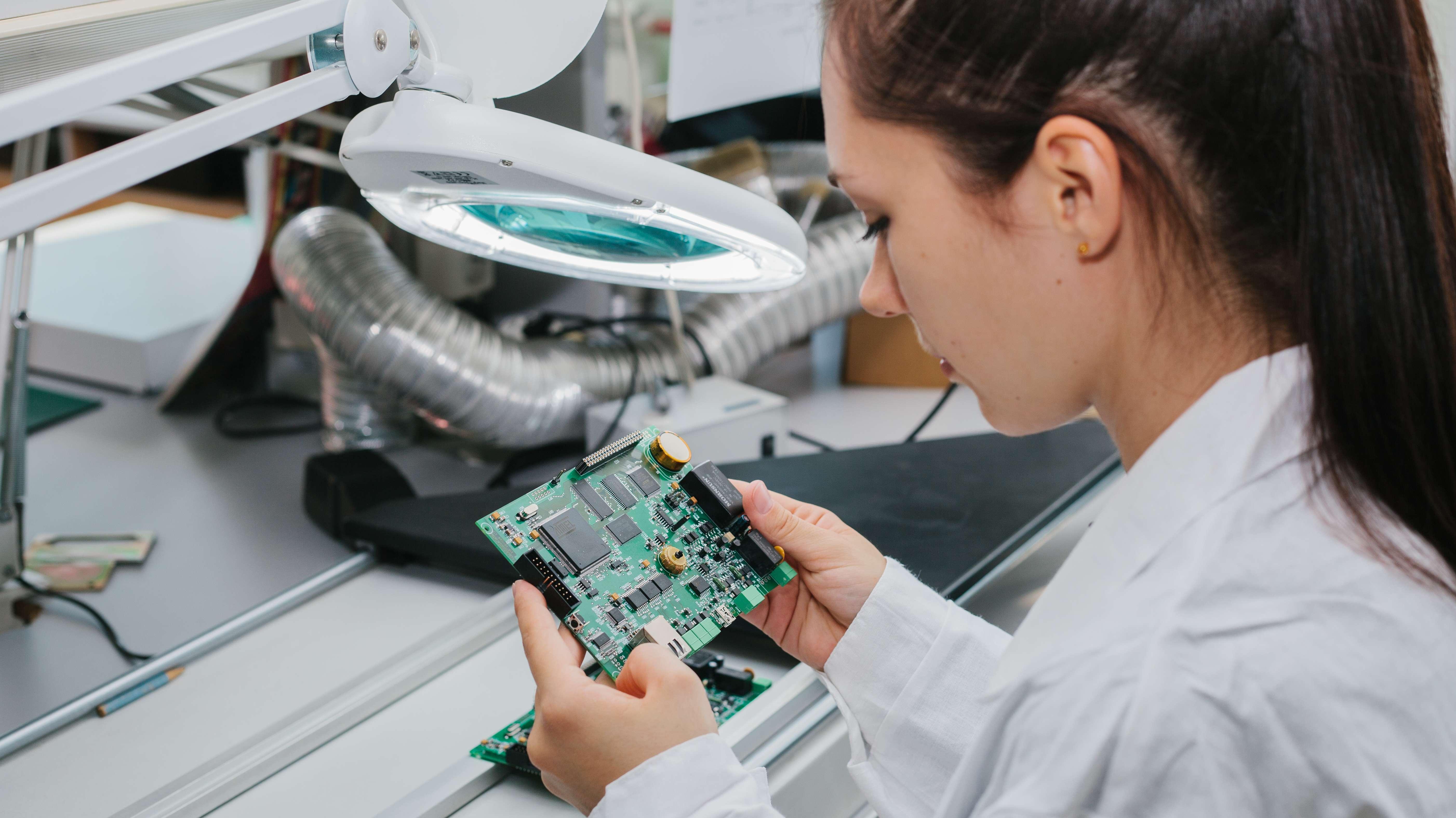 Eine Frau untersucht eine Computerplatine