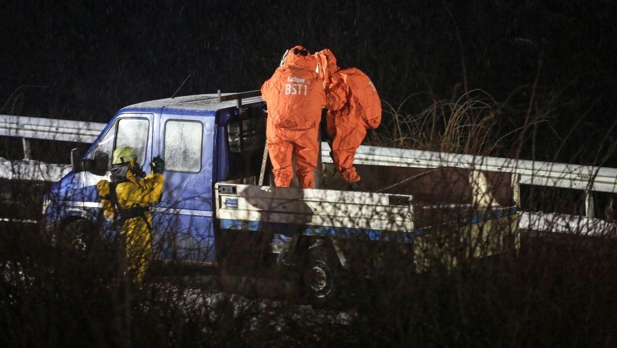 Zwei Männer in Schutzanzügen stehen auf der Ladefläche eines Kleintransporters.