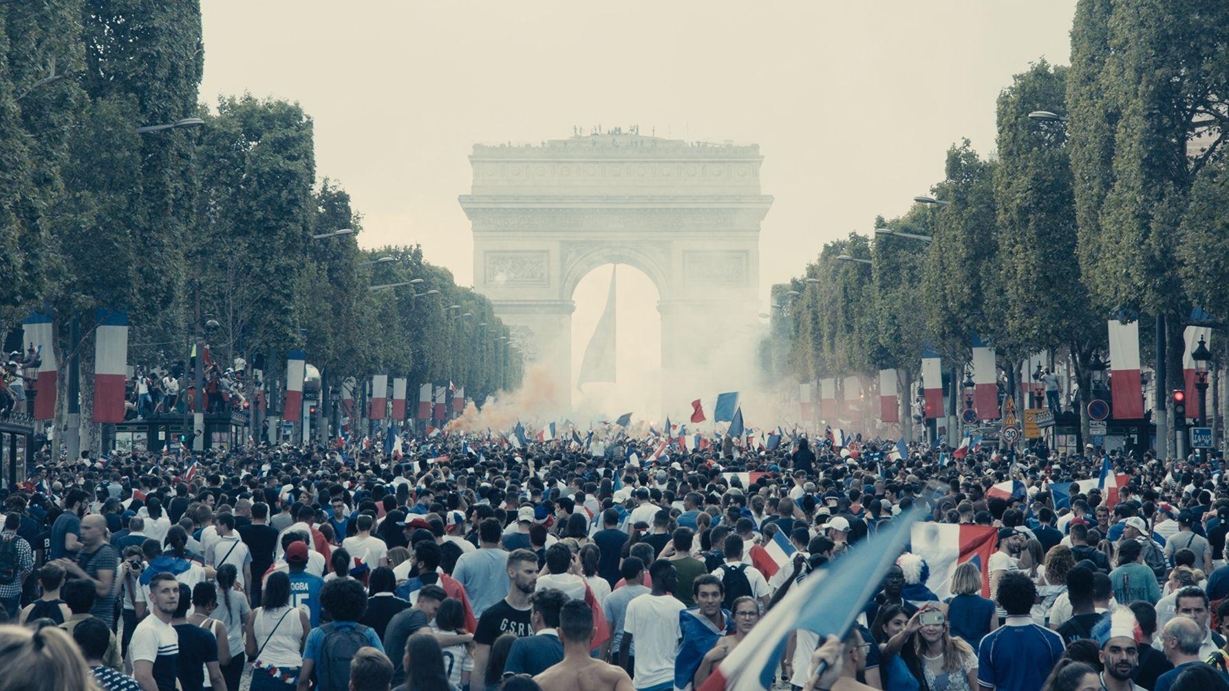 """Die von Trikoloren gesäumte Straße vor dem Arc de Triomphe ist von Menschen geflutet (Szene aus """"Les Misérables"""")"""