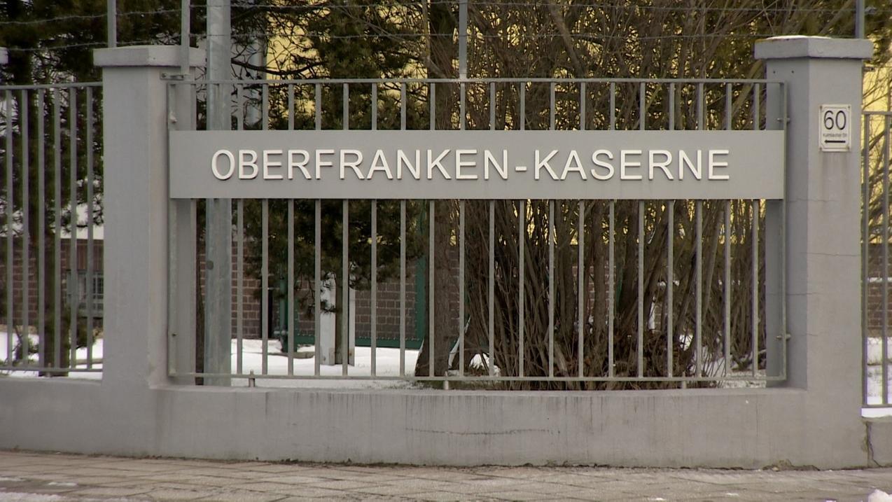 """Schild """"Oberfranken-Kaserne"""" an einem Zaun"""