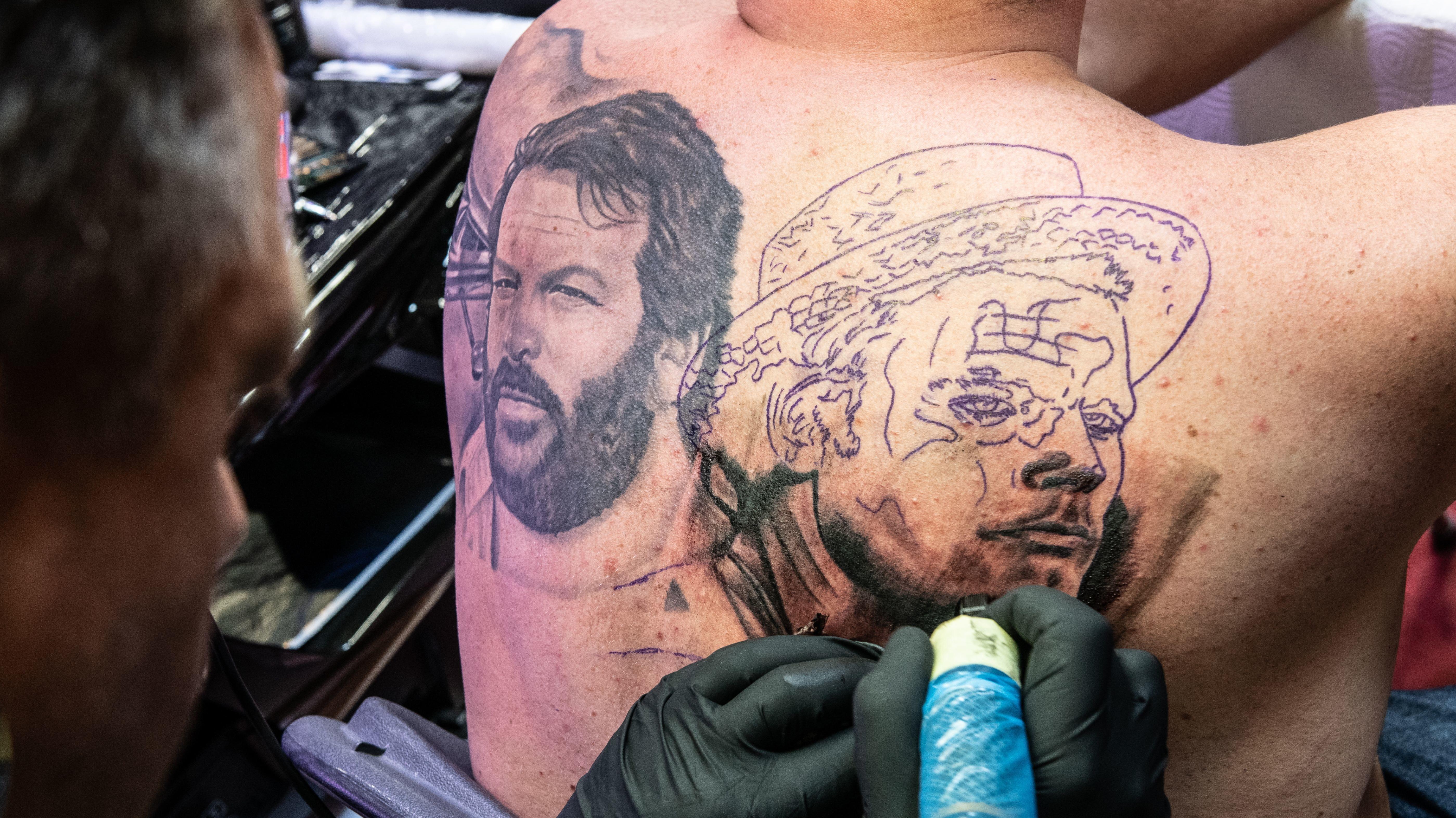 Ein Mann lässt sich neben das Porträt von Bud Spencer noch das Gesicht von Terence Hill stechen.