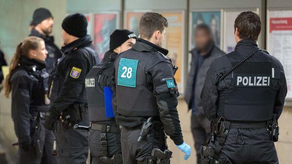 Polizisten umstellen einen dunkelhäutigen Mann während einer Polizeikontrolle am Frankfurter Hauptbahnhof.