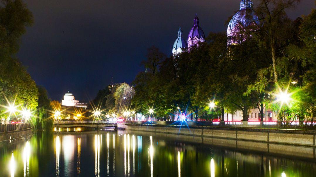 Das Deutsche Museum (M) und die St. Lukas Kirche spiegeln sich auf der Wasseroberfläche der Isar.