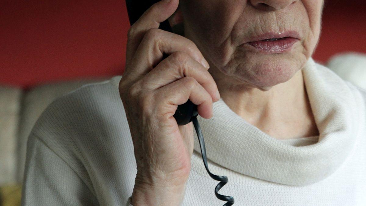Eine ältere Dame hält einen Telefonhörer