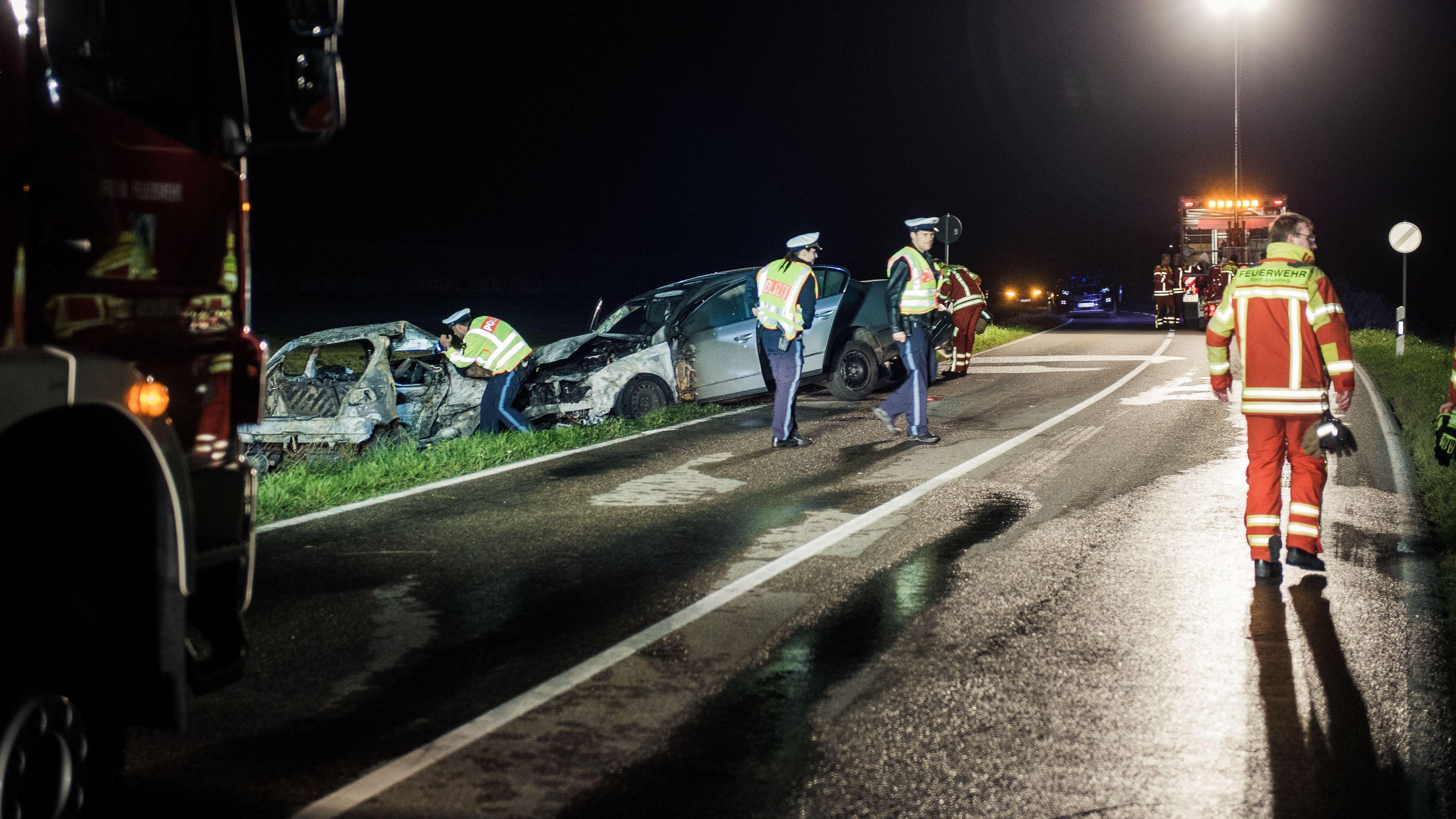 Polizisten nehmen die Unfallstelle mit zwei ausgebrannten Autos in Augenschein