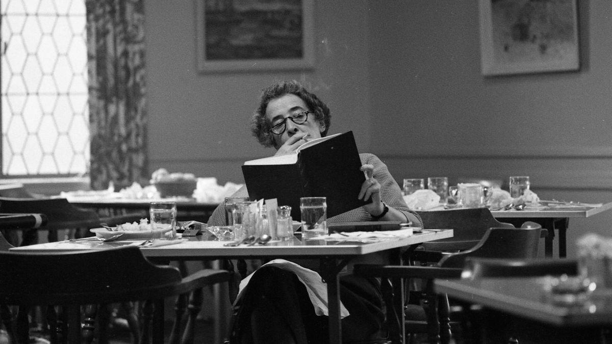 Hannah Arendt sitzt rauchend in einer menschenleeren Kantine und liest ein Buch