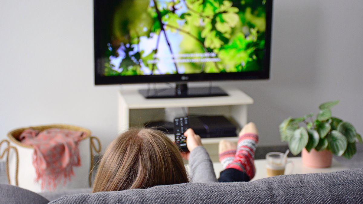 Eine junge Frau sitzt auf einer Couch und sieht fern.