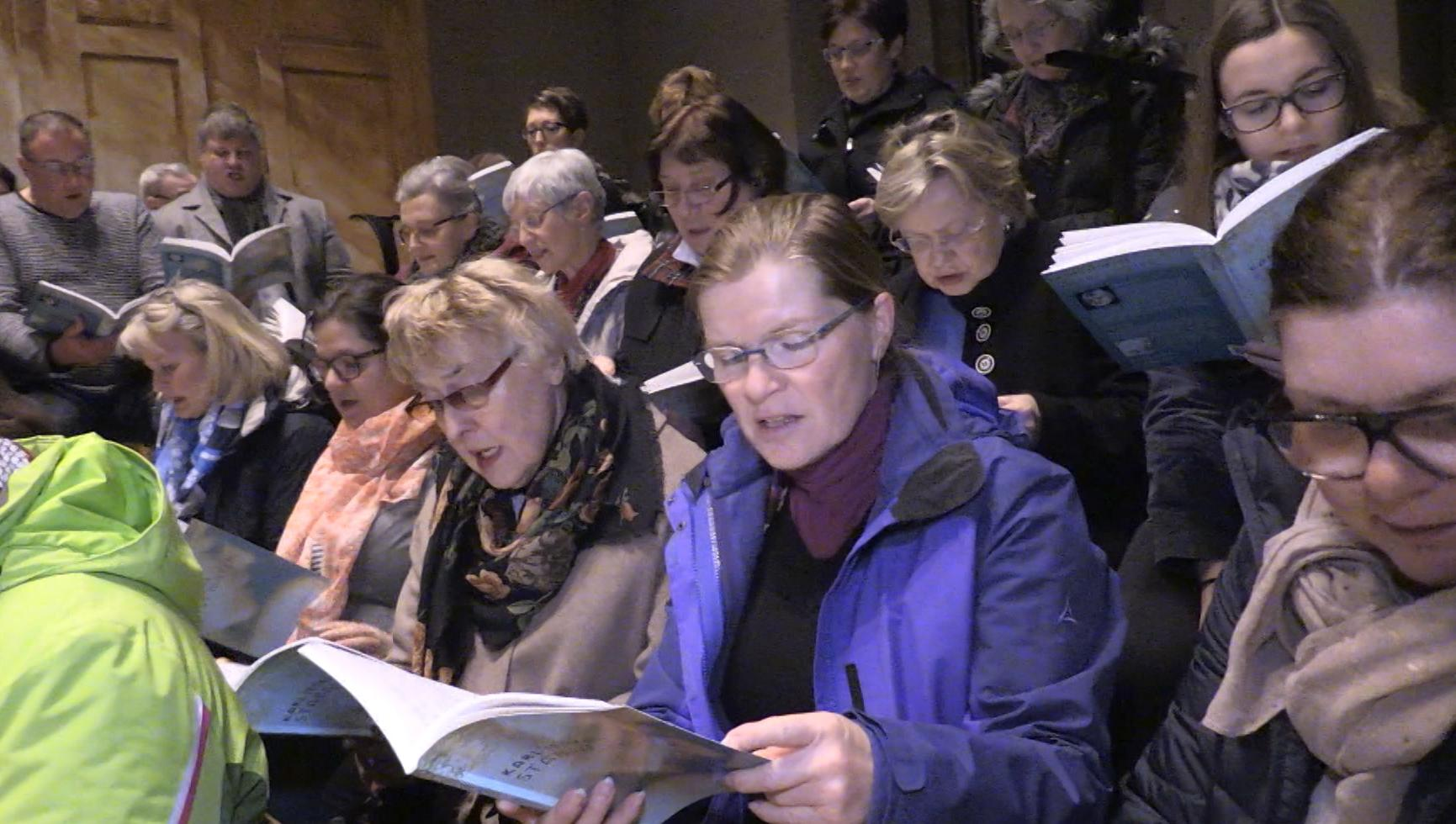 Die Sängerinnen und Sänger aus Schwabmünchen schauen konzentriert in ihre Noten.