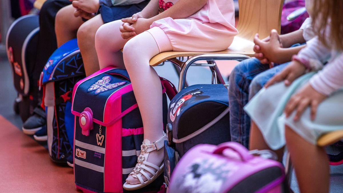 Mädchen und Jungen sitzen mit ihren neuen Schulranzen auf einer Bank.