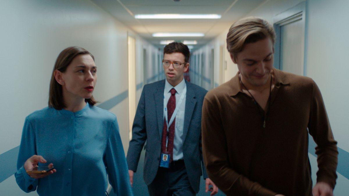 Die Schauspielerin Christiane Paul und zwei jüngere Herren gehen einen Bürogang entlang.