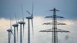 Symbolbild: Windräder und ein Strommast stehen in der Landschaft.    Bild:dpa-Bildfunk/Julian Stratenschulte