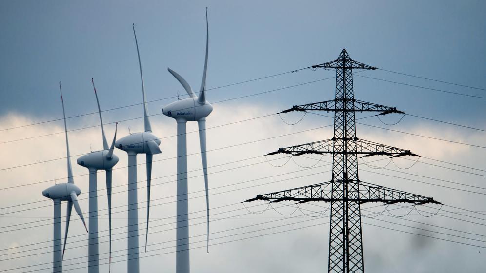 Symbolbild: Windräder und ein Strommast stehen in der Landschaft.  | Bild:dpa-Bildfunk/Julian Stratenschulte