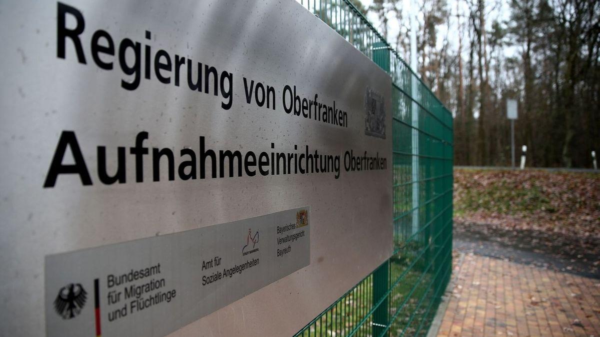 """Am Zaun der Asylbewerberunterkunft in Bamberg ist ein Schild befestigt mit der Aufschrift """"Aufnahmeeinrichtung Oberfranken""""."""