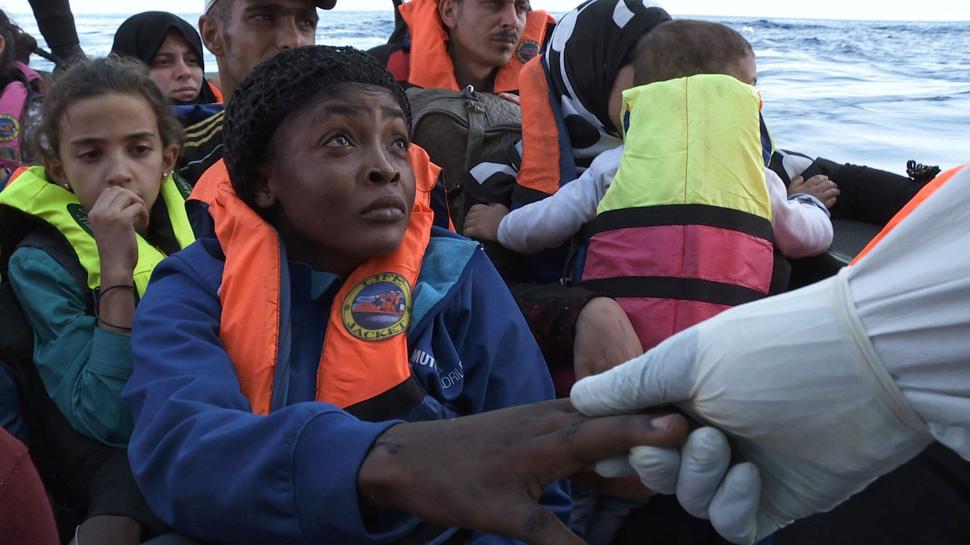 Eine Frau auf einem Flüchtlingsboot greift nach der Hand eines Retters