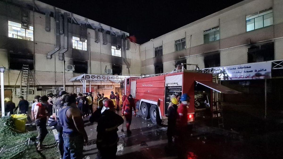 Feuerwehr und Helfer vor einem abgebrannten Krankenhaus in Bagdad.