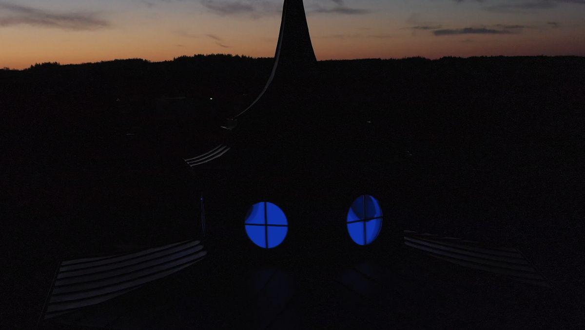 Die Kirche St. Maria in Ursberg ist von innen blau beleuchtet.