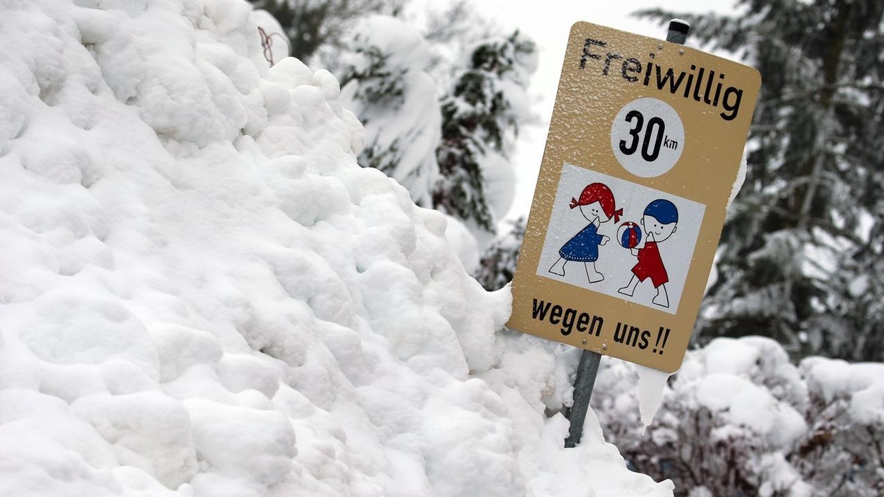 Aitrang: Ein Hinweisschild auf spielende Kinder steht in einem Schneehaufen.