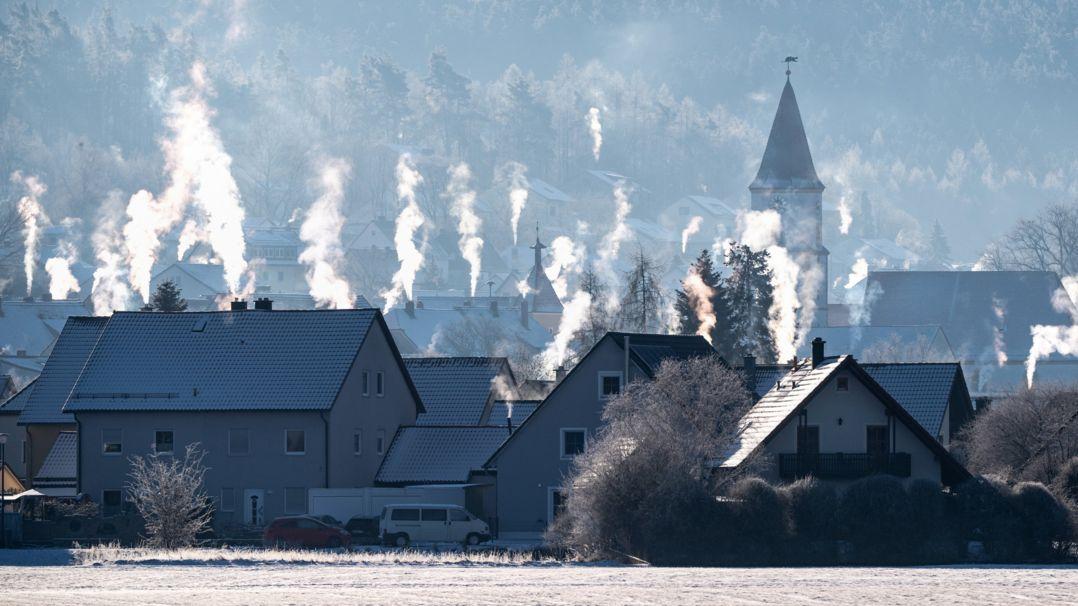 Heizungsabgase steigen über einer winterlichen Siedlung nach oben