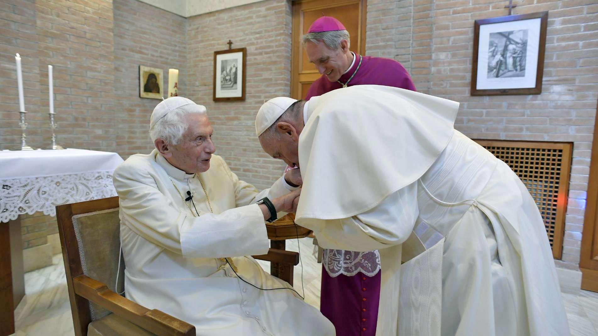 Papst Franziskus (r.) besucht seinen Vorgänger Benedikt XVI. und küsst ihm dabei die Hand. Im Hintergrund steht Georg Gänswein.