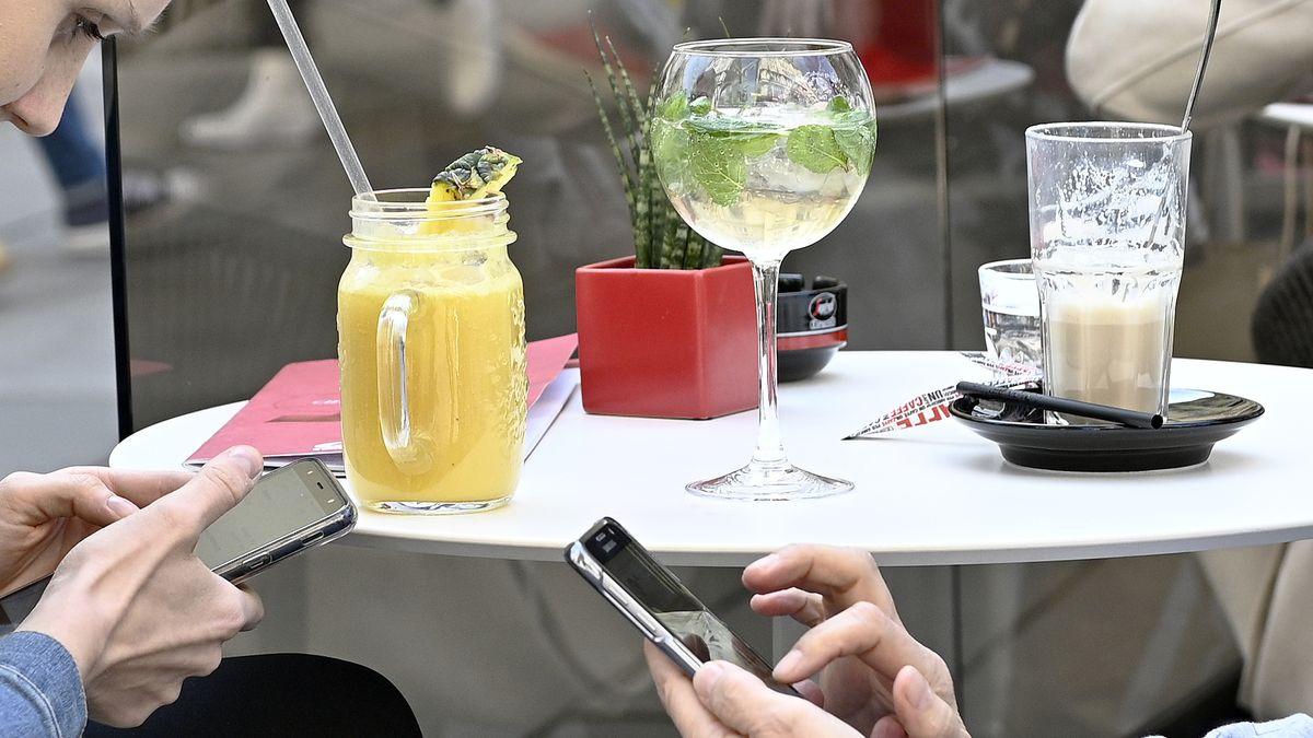 """Illustration zum Thema """"Menschen besuchen anl. der warmen Frühlingstemperaturen die Schanigärten"""": Tisch mit Cocktails und Latte Macchiato, zwei Personen, die am Smartphone beschäftigt sind, aufgenommen am Stephansplatz in Wien."""