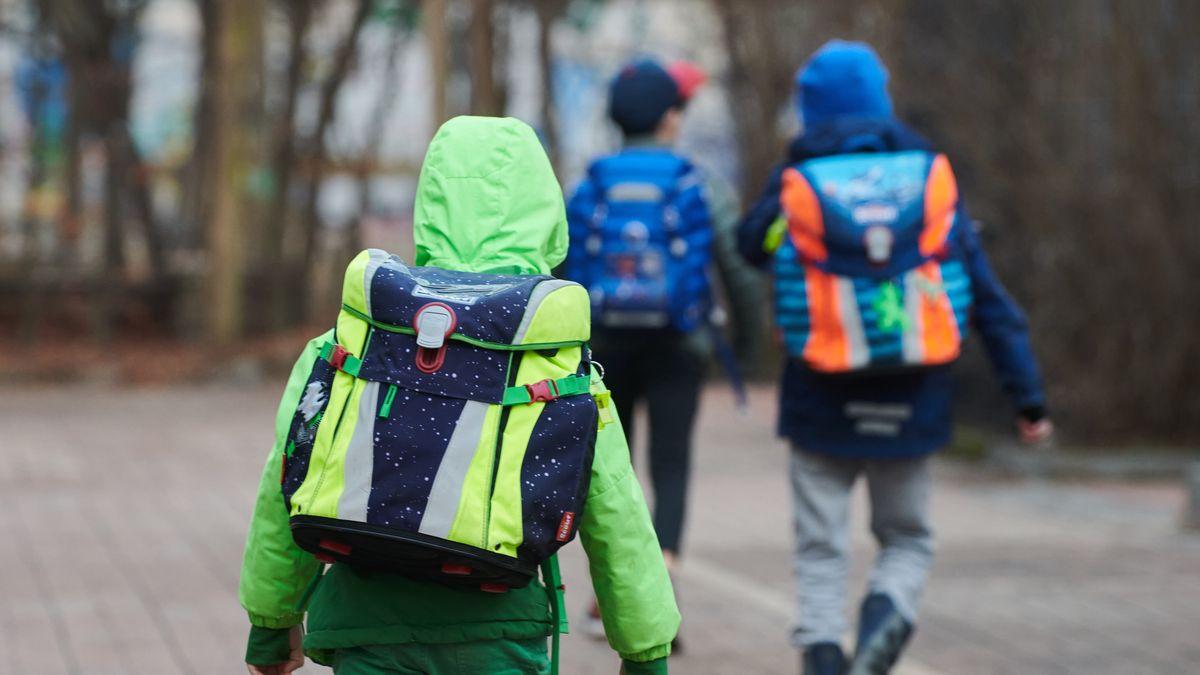 Drei Schüler gehen mit Schulranzen zum Eingang einer Grundschule