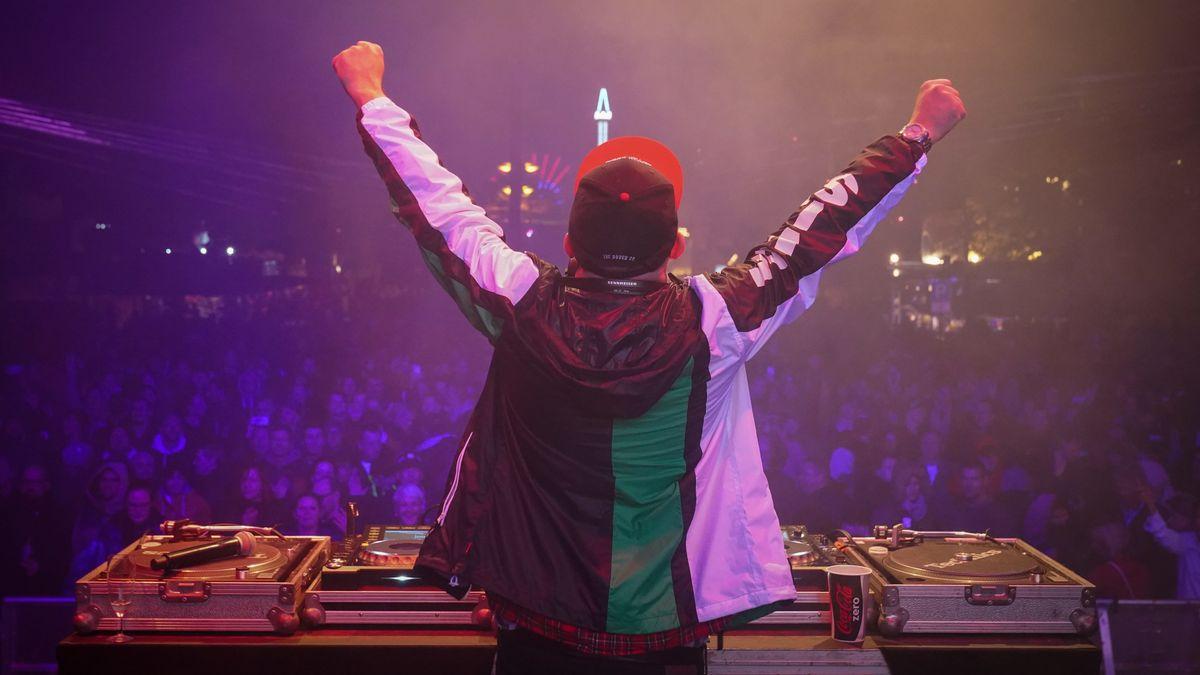 Rückenansicht eines DJ , der in einem mit violettem Licht beleuchteten großen Saal von einer Masse Fans bejubelt wird.