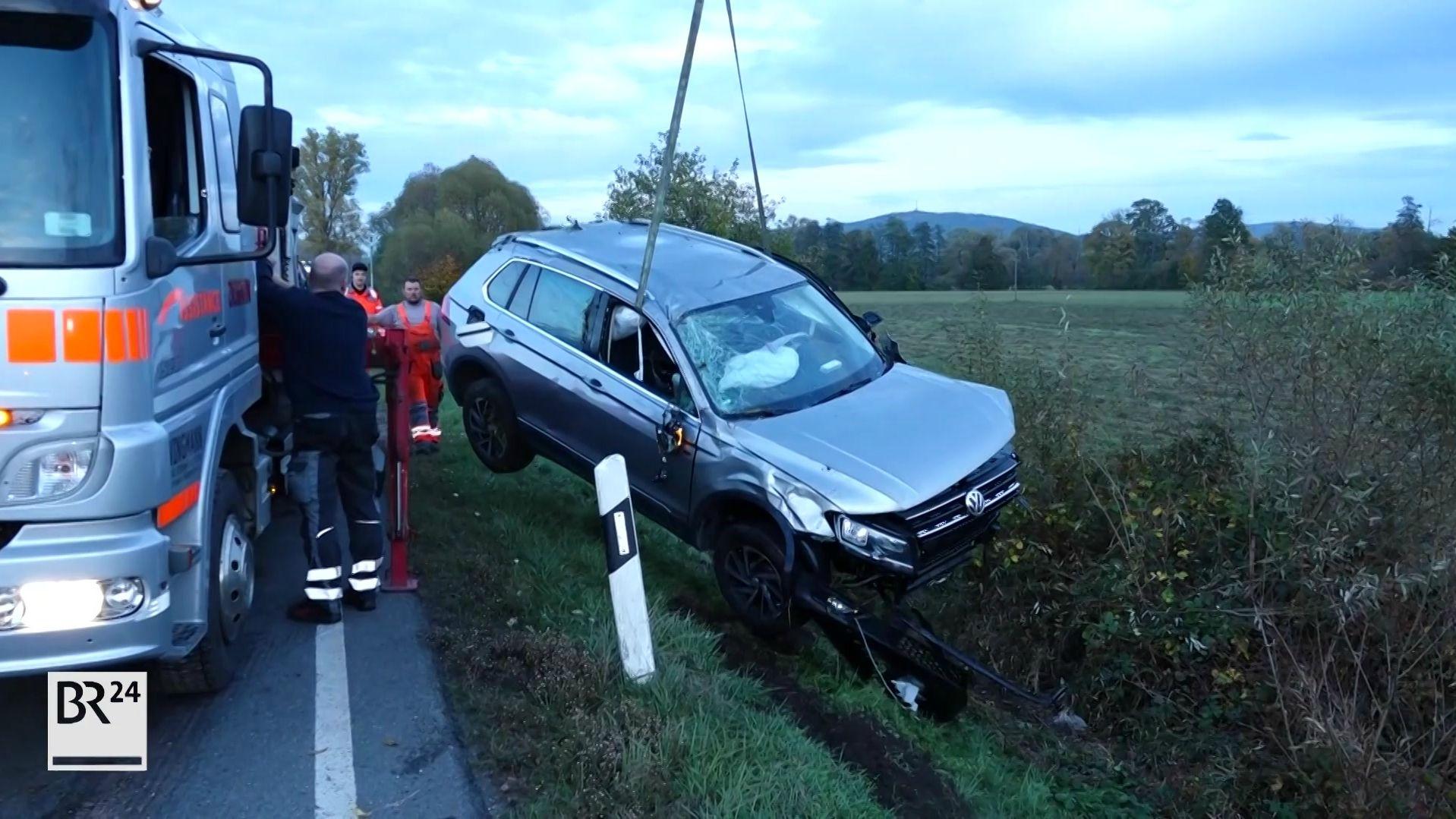 Ein Auto hängt an einem Kran und wird aus dem Straßengraben geborgen.