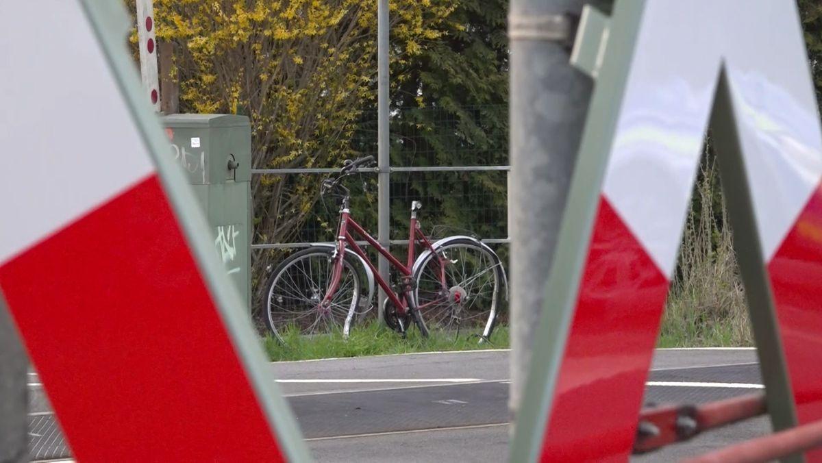 Nahe des Bahnübergangs steht das rote Fahrrad des Opfers, angelehnt an ein Geländer.