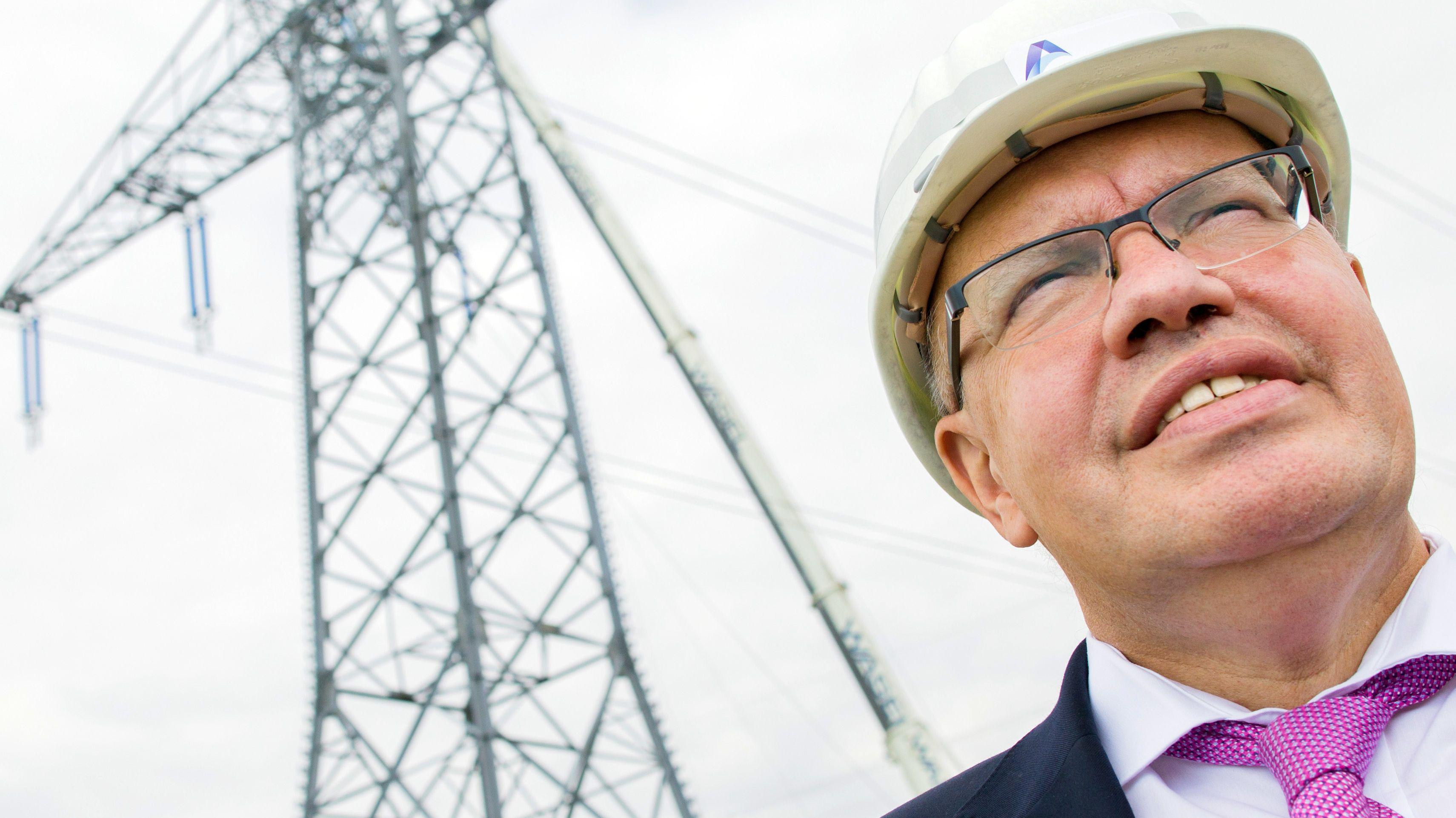 Wirtschaftsminister Altmaier vor Strommasten
