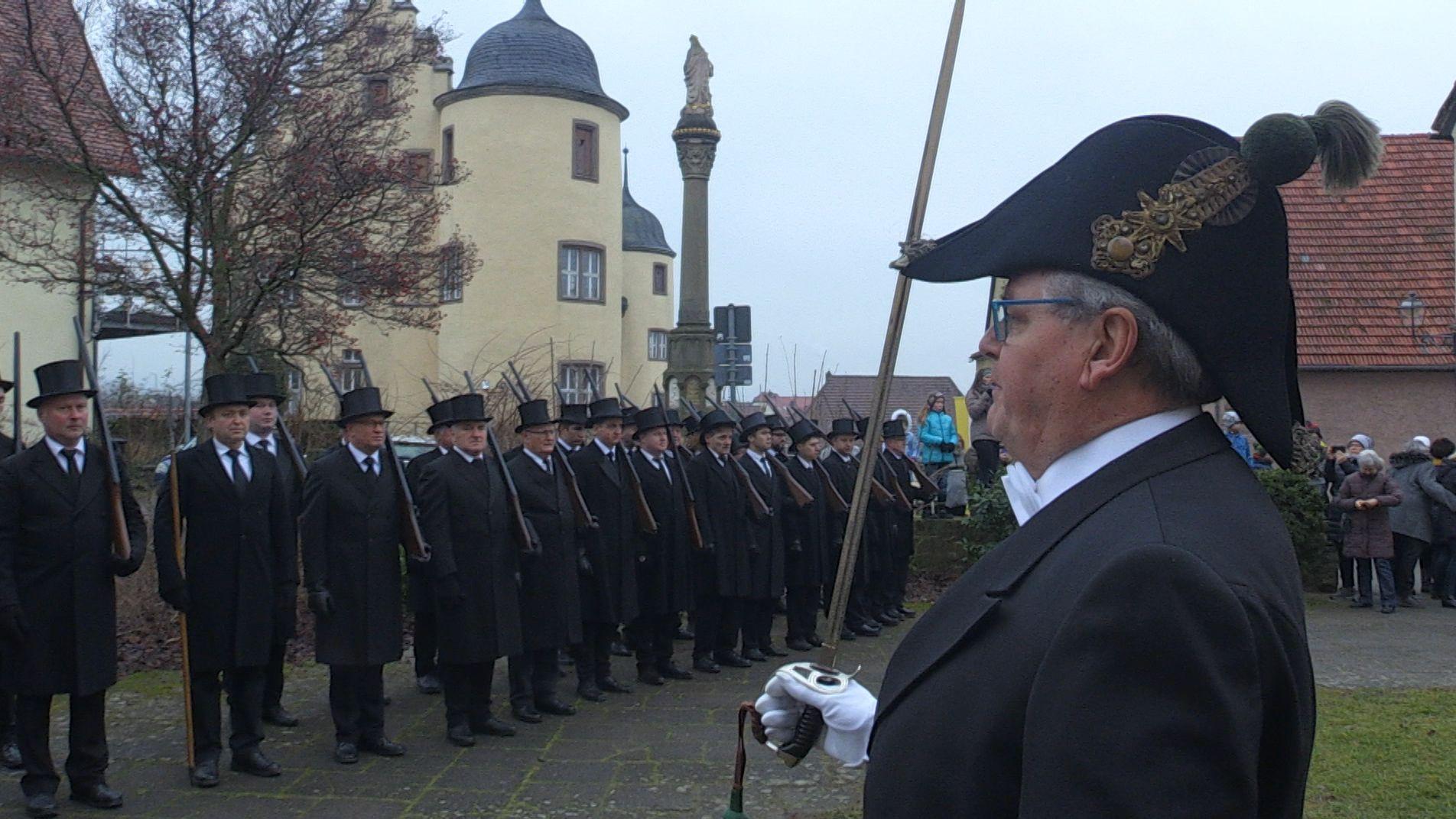 Die Oberschwarzacher Bürgerwehr ist traditionell in Frack und Zylinder gewandet mit ihren Holzgewehren vor ihrem Hauptmann Georg Wagner angetreten. Dieser grüßt mit dem Säbel.