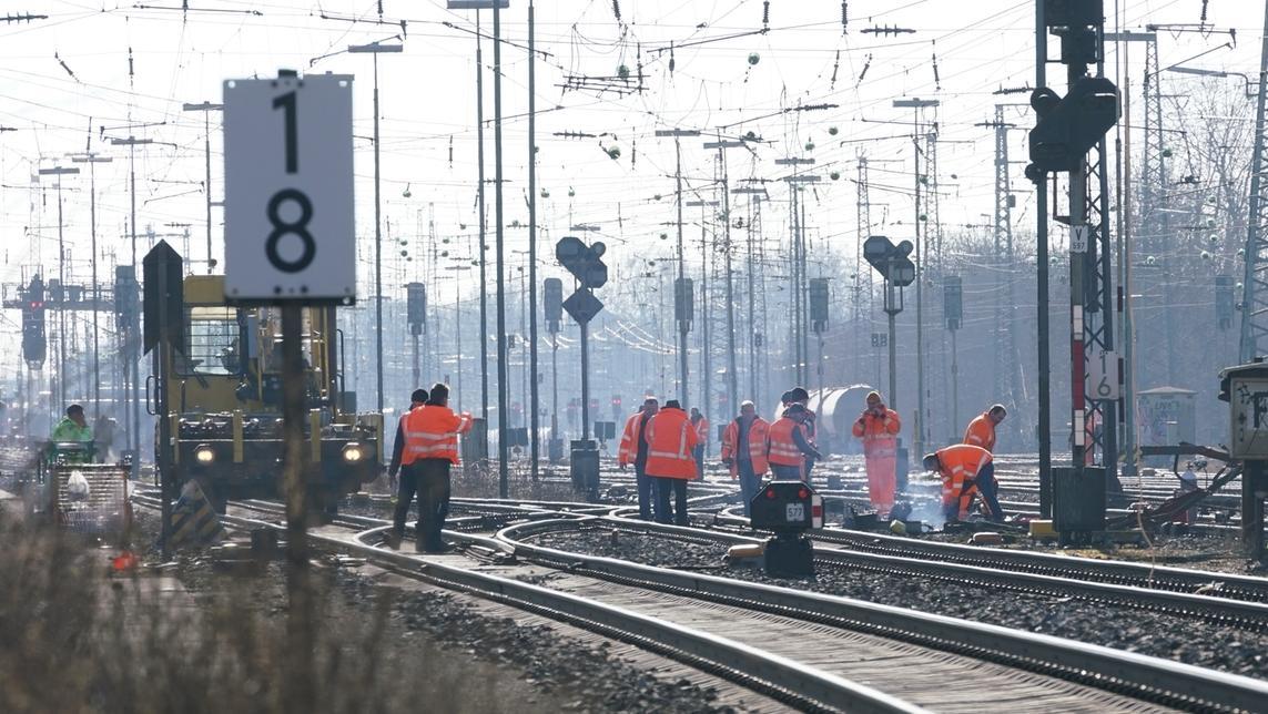 Mehrere Personen in orangefarbenen Warnwesten stehen auf den Gleisen in der Nähe des Bahnhofs Augsburg-Oberhausen