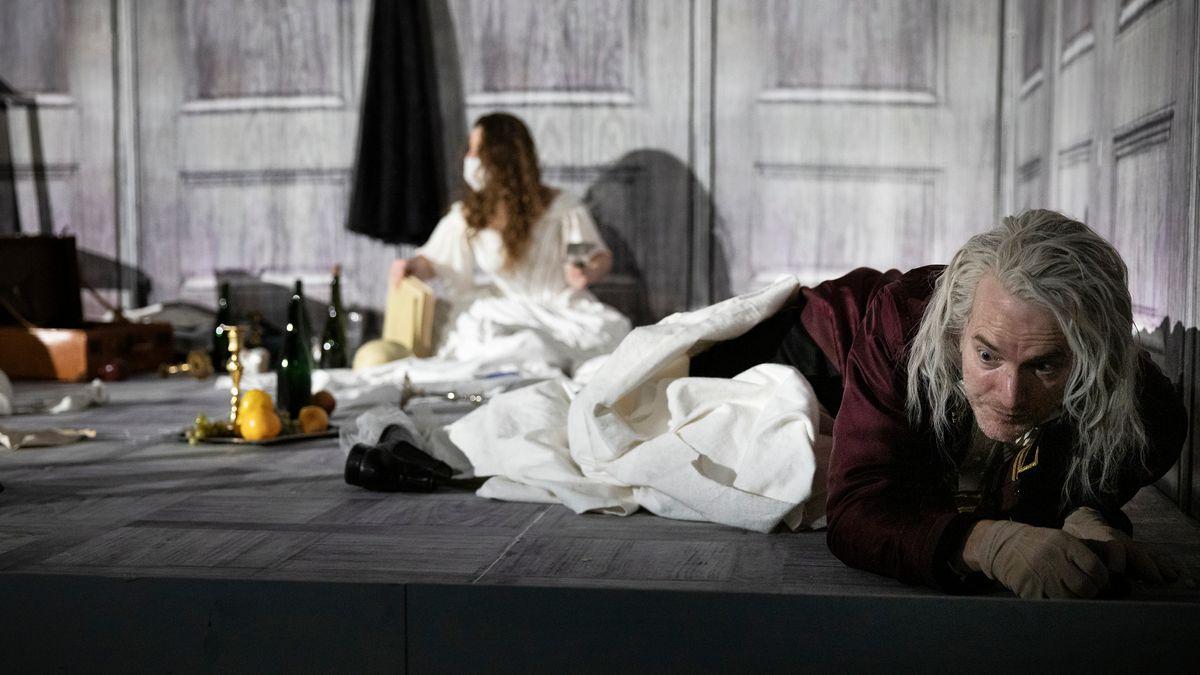 """Mann mit langen gruauen Haaren liegt bäuchlings zwischen Stilleben und Decken auf der Erde, an der Wand hinter ihm sitzt eine maskierte FrauSzene aus """"Isola"""" am Staatstheater Nürnberg"""