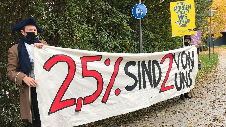 """Künstler protestieren und halten ein Banner mit der Aufschrift """"2,5 % sind 2 von uns""""."""