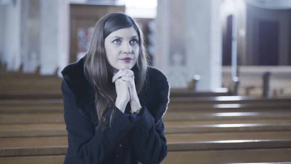 Jacqueline Straub sitzt mit gefalteten Händen in einer Kirchenbank. | Bild:BR / Christian Wölfel