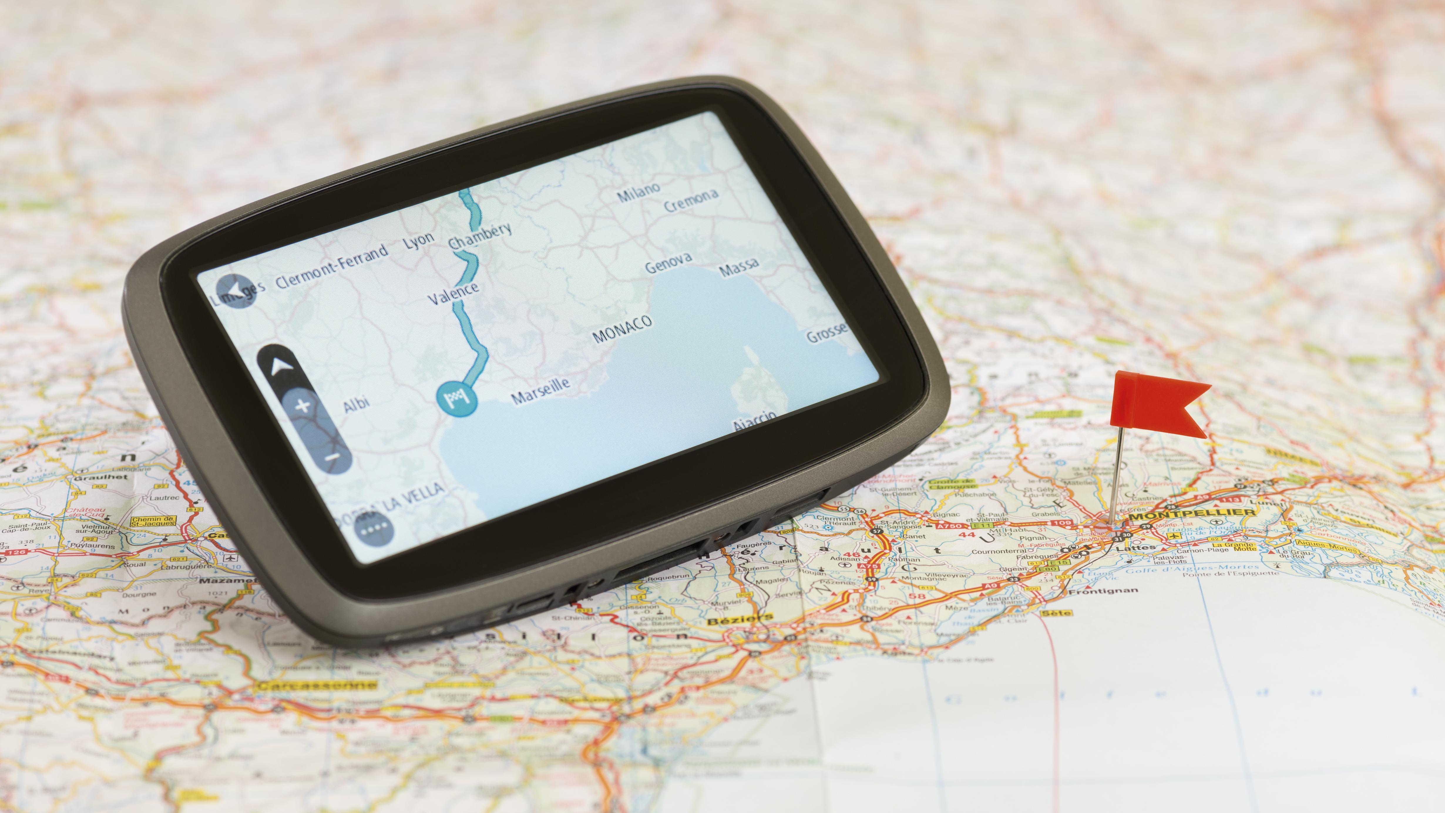Ein Navigationsgerät liegt auf einer Landkarte