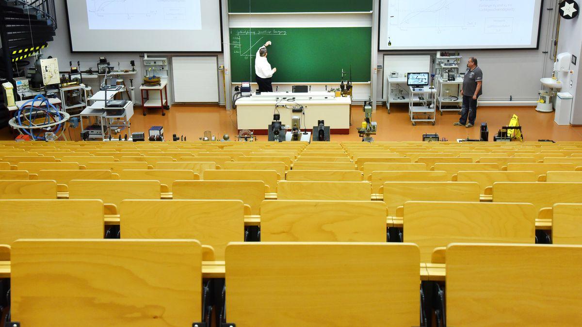 Ein Dozent bereitet sich in einem leeren Hörsaal auf eine Vorlesung vor.