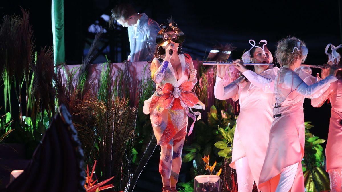 Die isländische Musikerin Björk und drei Flötistinnen in extravaganten pinken Phantasiekleidern inmitten einer exotischen Pflanzenwelt