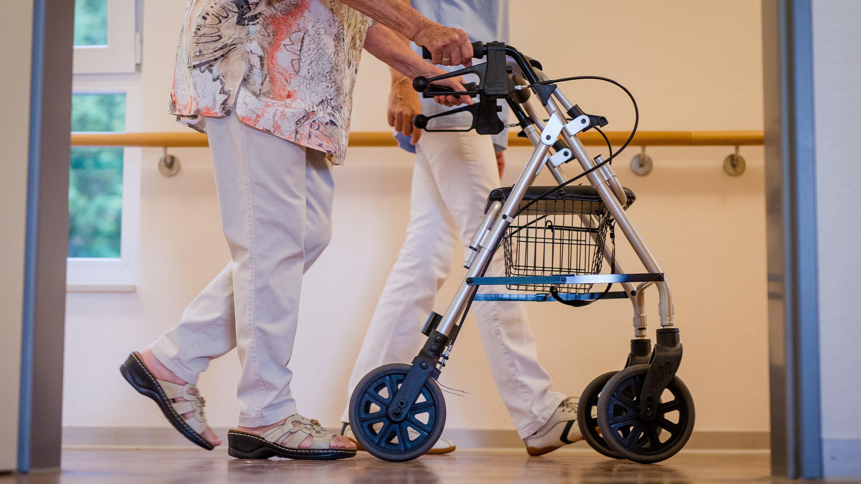 ARCHIV - 23.08.2018, Baden-Württemberg, Stuttgart: Eine Pflegekraft geht in einem Pflegeheim mit einer älteren Dame.