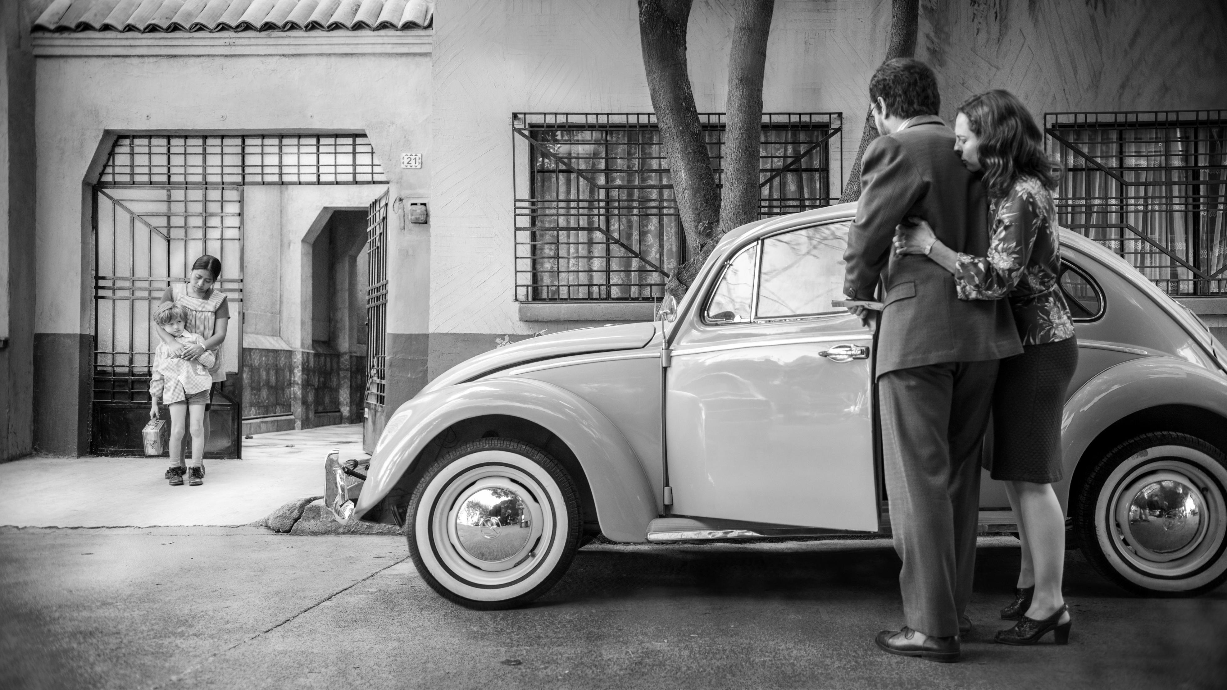 """Filmszene aus """"Roma"""": Ein Paar neben einem VW-Käfer vor einem Haus, Kindermädchen und Kind stehen vor dem Hoftor."""