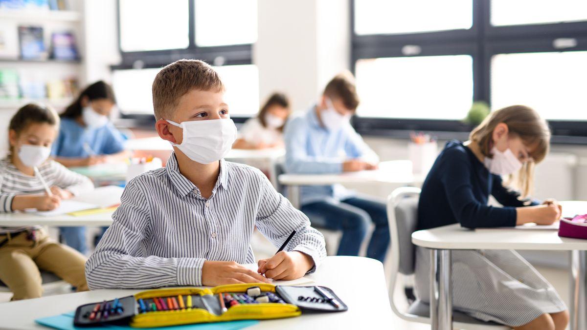 Schüler sitzen mit Maske im Schulunterricht