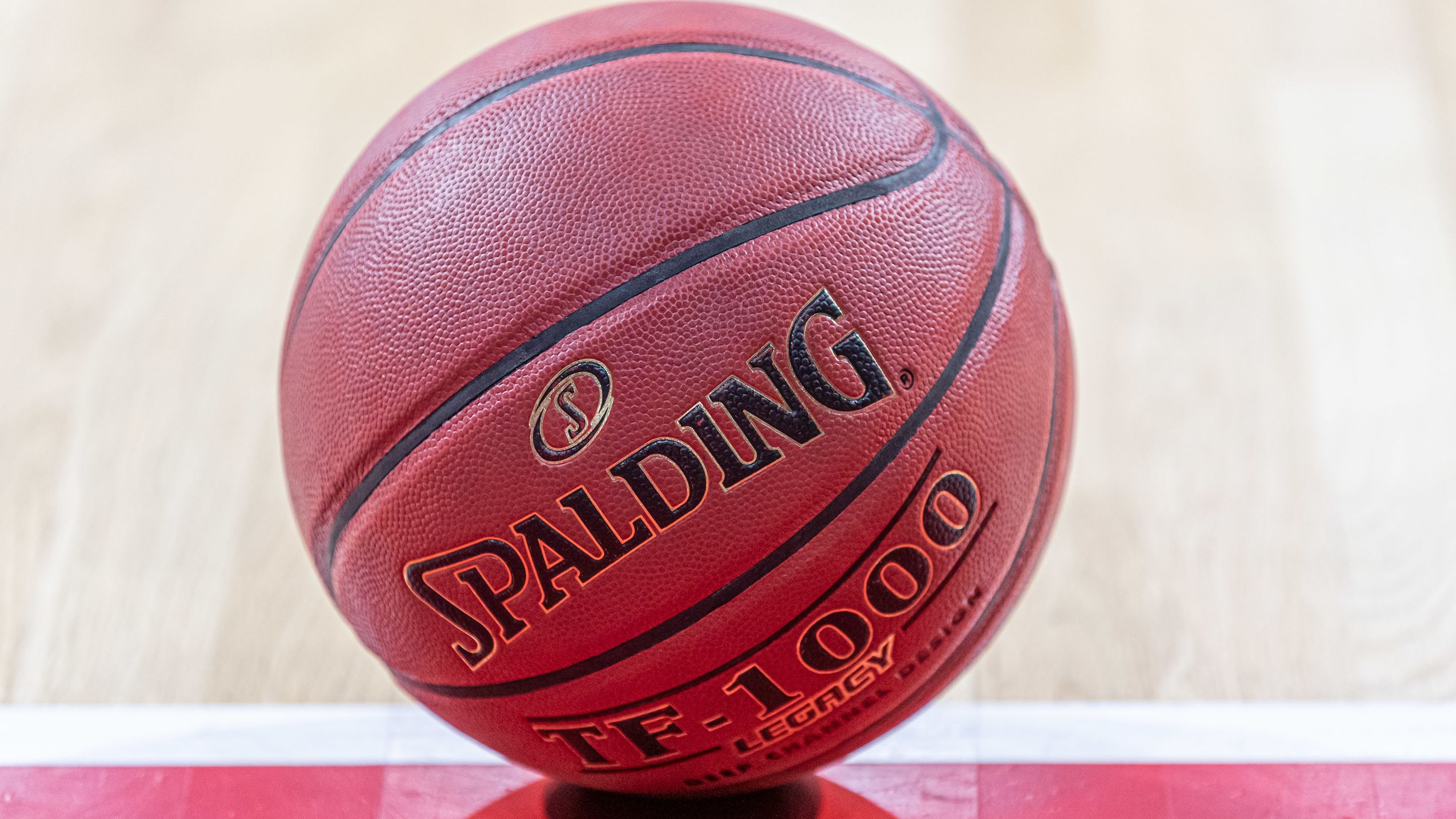 Ein Basketball liegt auf dem Hallen-Parkett.