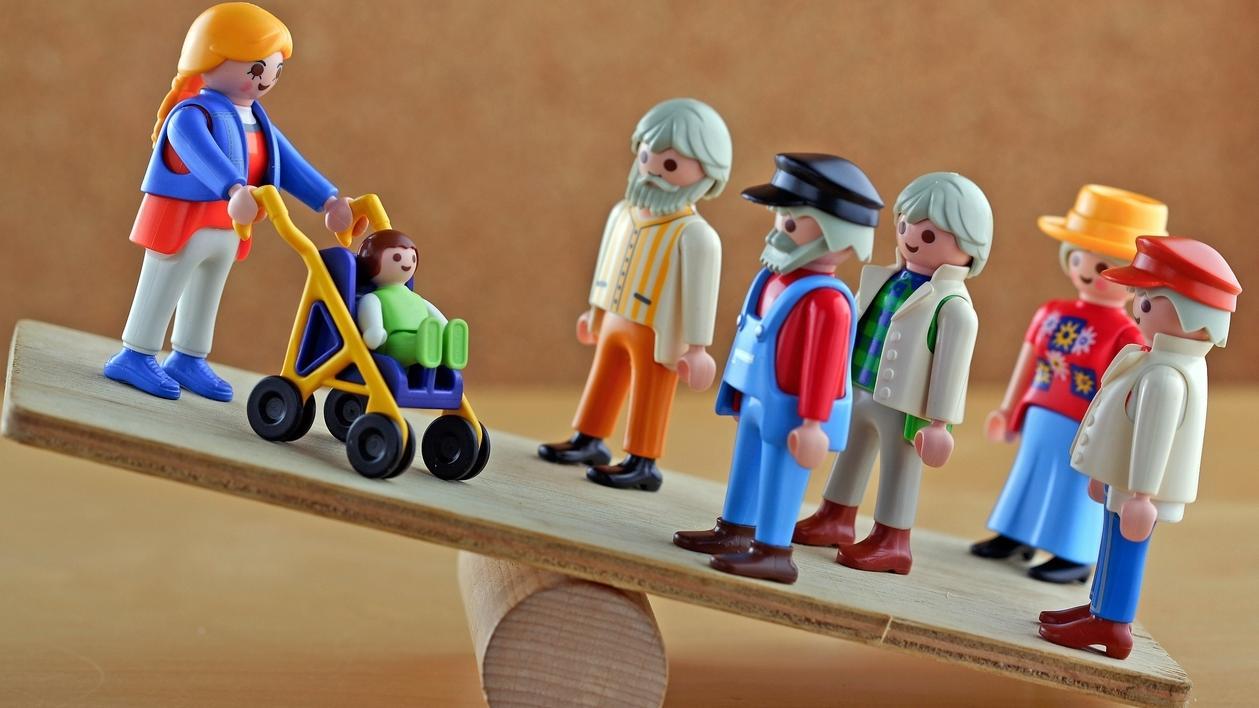 Alte und junge Playmobildmännchen auf einer Wippe
