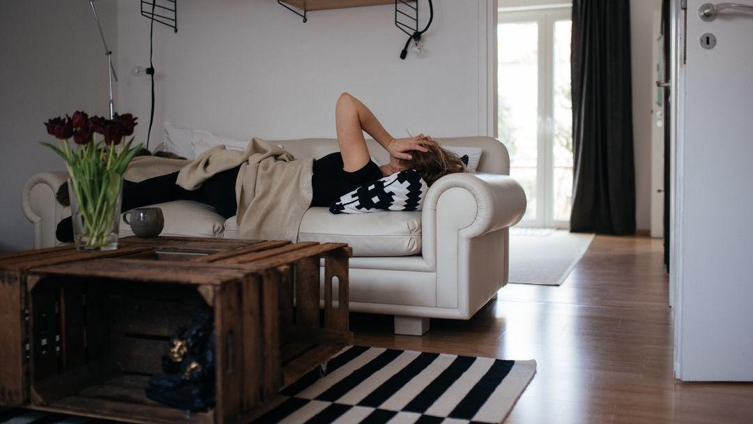 Post-Covid (Symbolbild): Eine Frau liegt erschöpft auf ihrer Couch.