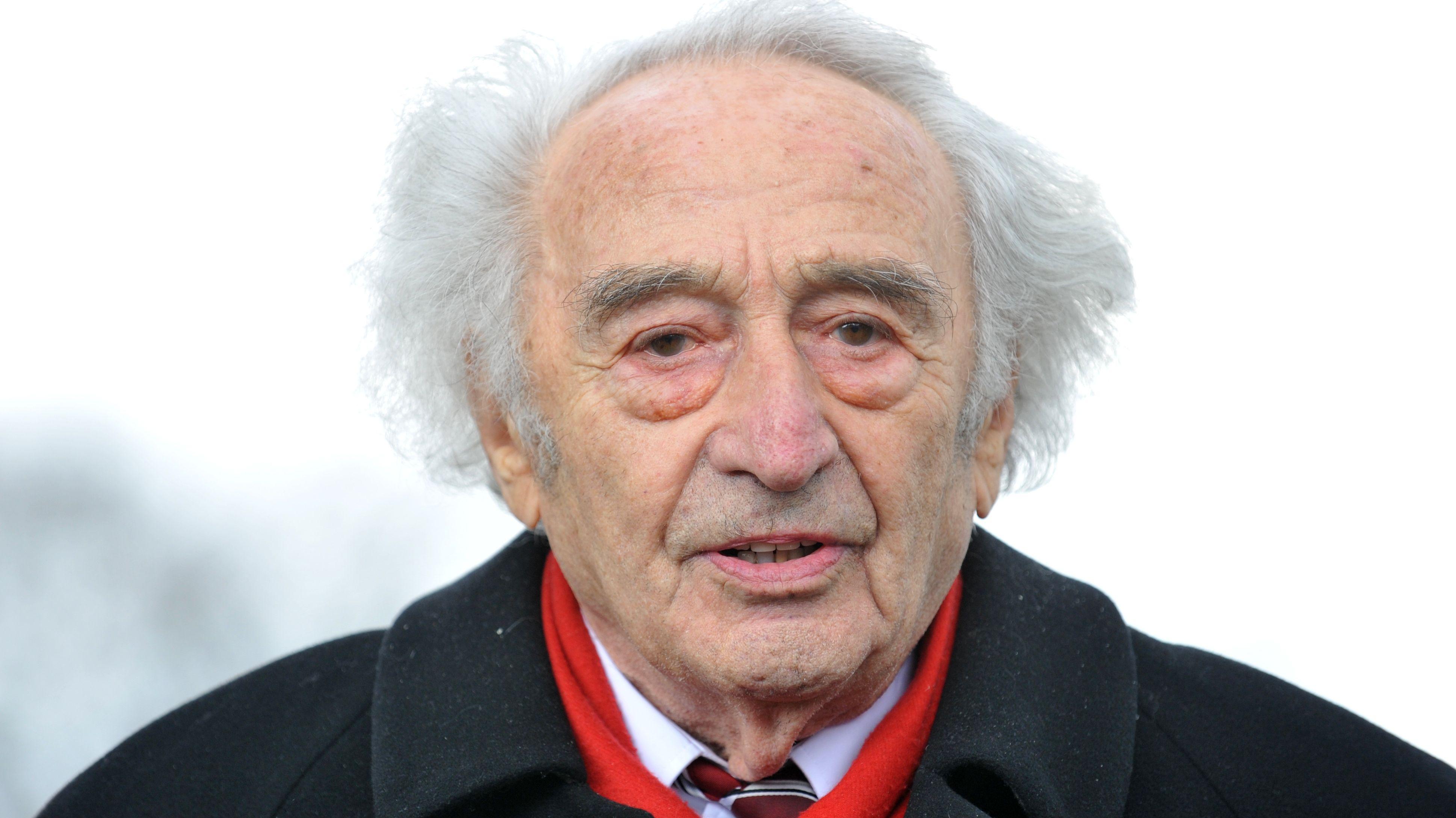 Porträtaufnahme von Max Mannheimer, er trägt einen schwarzen Mantel, Hemd, Krawatte und einen roten Schal.