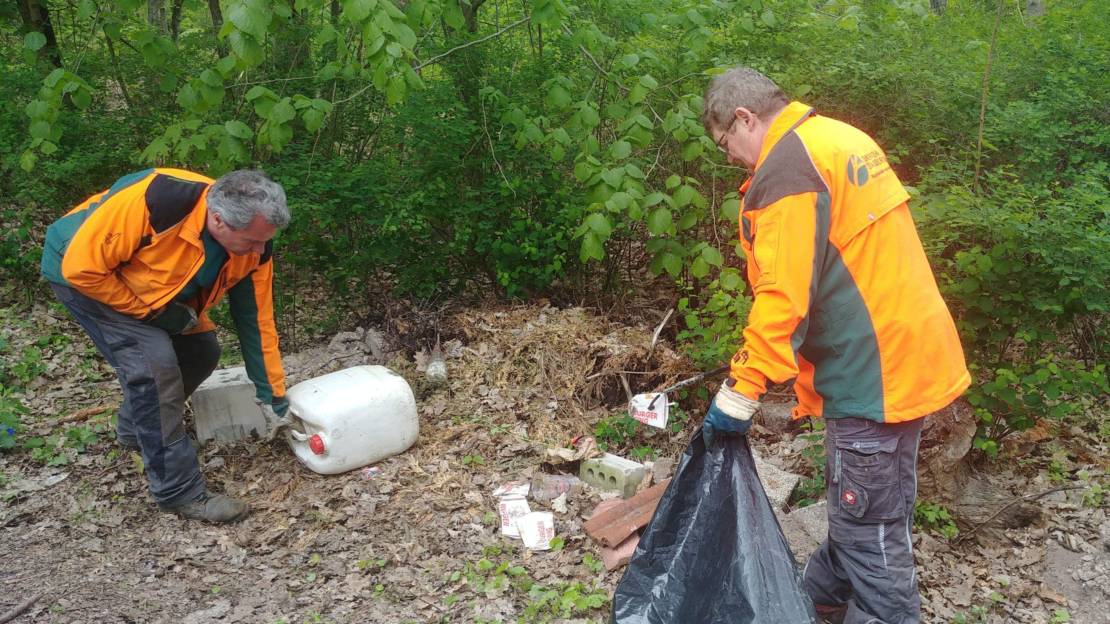 Zwei Männer sammeln Müll.