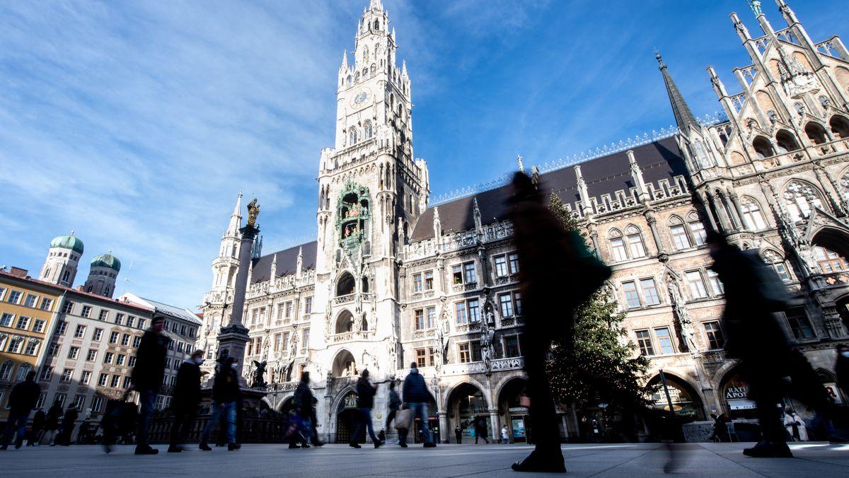 Passanten auf dem Münchner Marienplatz von dem Rathaus